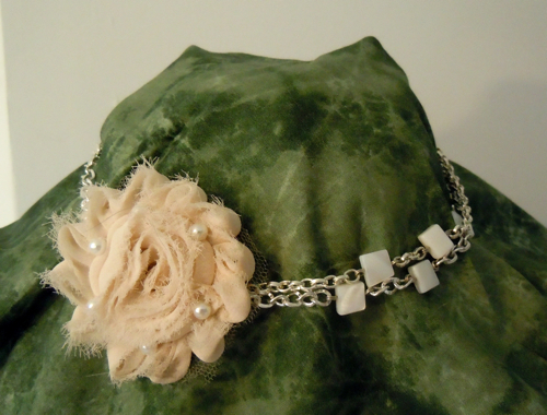 rosette necklace on a chain with small square shell beads